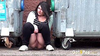 A bit plump amateur brunette gal squats down and pisses between refuse bins