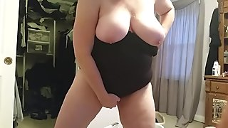 bbw wife putting on her black girdle over her big tits